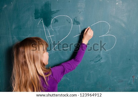 Young girl writing numbers on chalkboard with chalk - stock photo