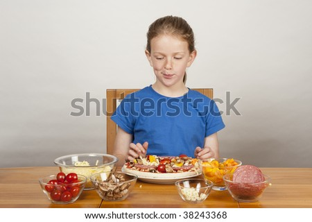 young girl (9 years old) making home-made pizza - stock photo