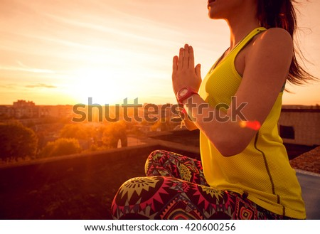Young girl yoga on the roof. Silhouette at the sunset