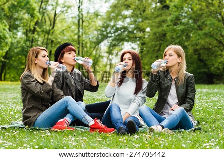Young girls are sitting in the park and drinking water.Refreshment for young girls