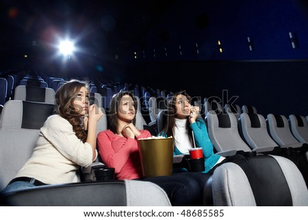 Young girls at viewing of sad cinema - stock photo
