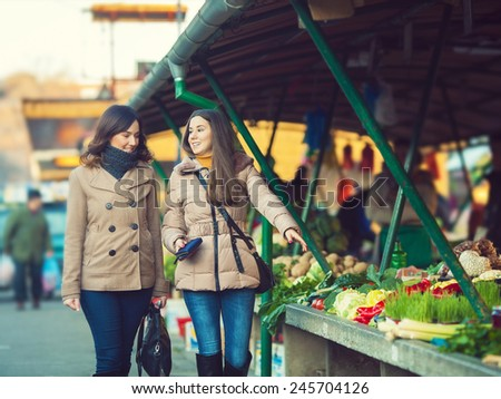 Young girls buying fresh organic food on the market - stock photo
