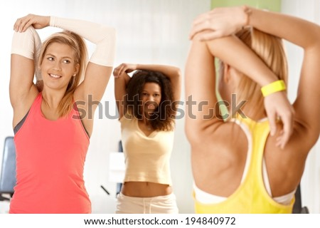 Young girls doing stretching exercises in group, looking at fitness instructor. - stock photo