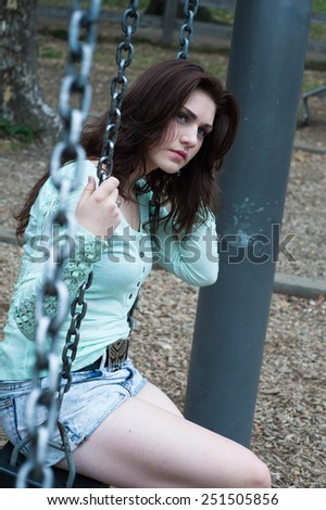 Young girls full of thoughts sitting on swings in the park - stock photo