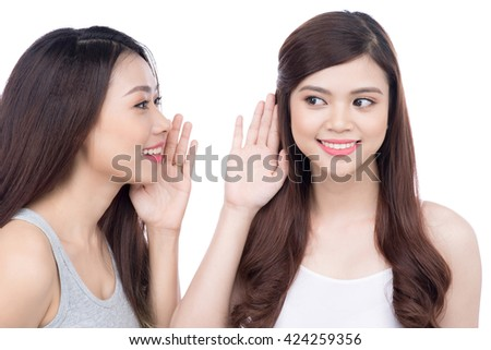 Young girls gossiping some secret over white  - stock photo