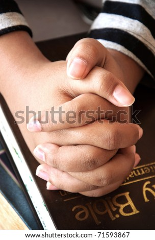 Young girls hands clasped in prayer over a Holy Bible - stock photo