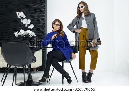 Young girls in coats posing at studio