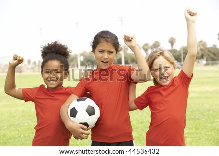 Young Girls In Football Team Celebrating - stock photo