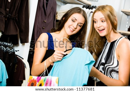 Young girls in the department store holding fashionable T-shirt