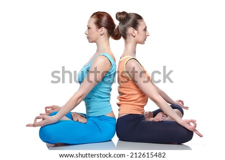 young girls practicing yoga on white background, meditating in lotus position. - stock photo