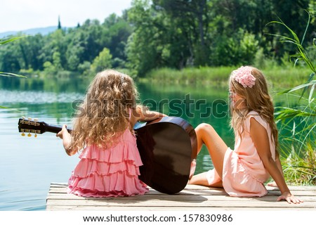 Young girls singing together with spanish guitar at lake. - stock photo