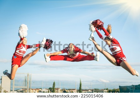 Young girls teenager cheerleaders team performing a jump with male coach - American style culture - High school college sports - stock photo