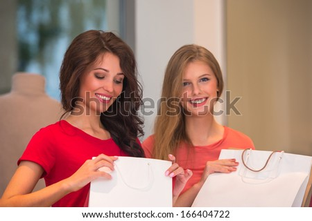 Young girls with shopping bags in store - stock photo