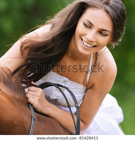 Young glad brunette woman wearing white dress rides brown horse at summer green park. - stock photo