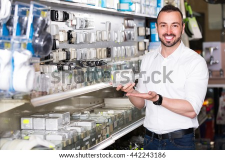 young glad european man picking electric plug in household shop - stock photo