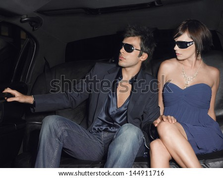 Young glamorous couple wearing sunglasses in limousine