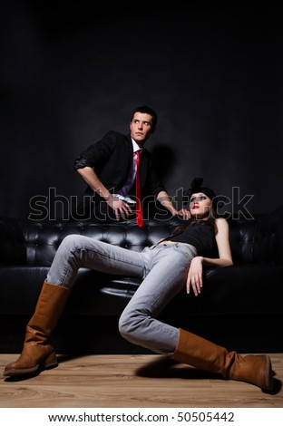 Young glamorous loving couple on a black sofa. Red tie and red lips.