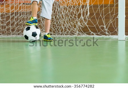 Young goalkeeper on an indoor court standing with one foot resting on the soccer ball, low angle view of his legs with copy space - stock photo