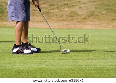 Young golf player preparing the final stroke