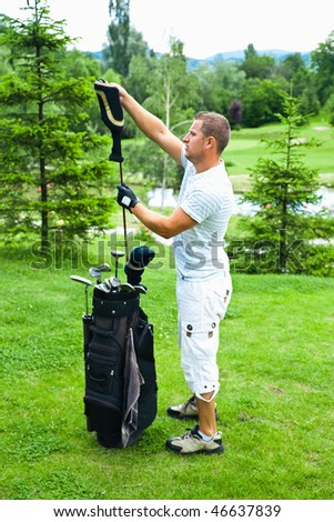 Young golfer arranging clubs in bag.