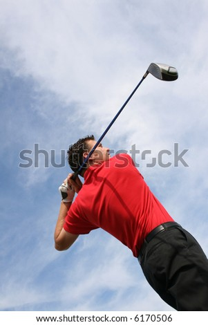 Young golfer at an angle hitting a driver - stock photo