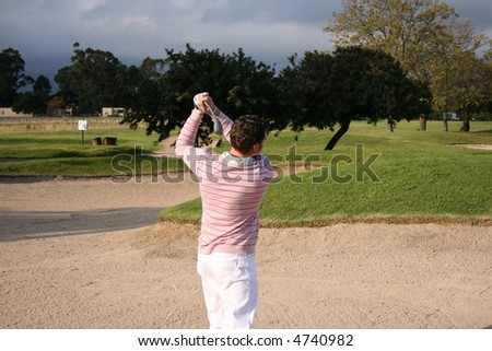 Young golfer following his ball after a bunker shot - stock photo