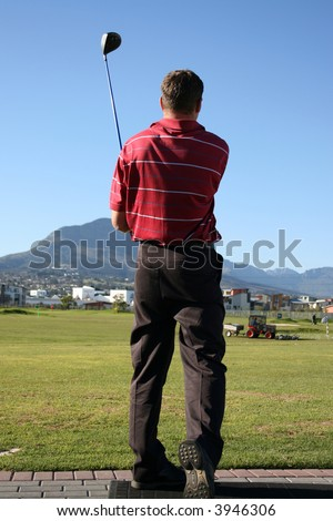 Young golfer following his golf shot on the range Follow Through of a young professional golfer whilst practising on the range - stock photo