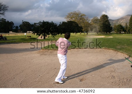 Young golfer hitting a bunker shot, the sand still in the air - stock photo