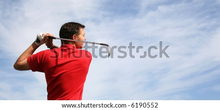 Young golfer hitting an iron against a half cloudy sky - stock photo