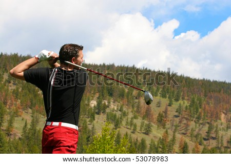 Young golfer in his follow through position with a driver - stock photo
