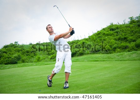 Young golfer in swing pose. - stock photo