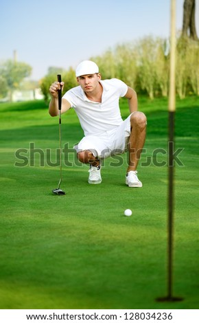 Young golfer lines up his eagle putt. - stock photo