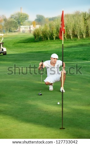 Young golfer lining up a putt - stock photo