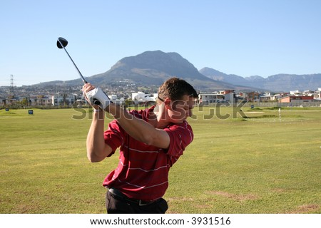 Young golfer on the driving range taking a back swing Follow Through of a young professional golfer whilst practising on the range - stock photo