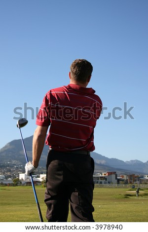 Young golfer on the range following his golf shot Follow Through of a young professional golfer whilst practising on the range - stock photo