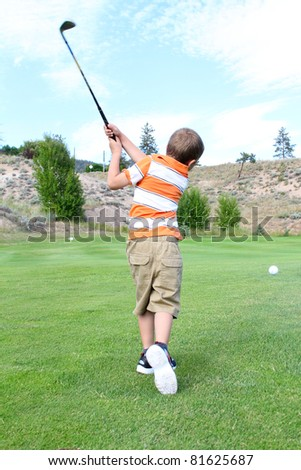 Young golfer playing a shot from the fairway - stock photo
