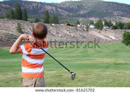 Young golfer playing a shot from the tee box - stock photo