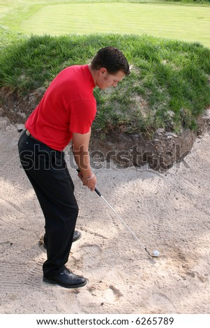 Young golfer preparing for a bunker shot - stock photo
