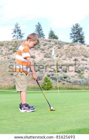 Young golfer putting his ball on the green - stock photo