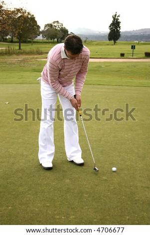 Young golfer putting on the greens on a course in South Africa - stock photo