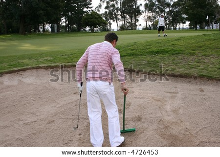Young golfer raking the bunker on the golf course - stock photo