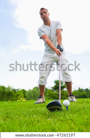 Young golfer ready for golf strike.