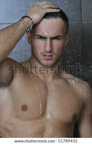 young good looking and attractive man with muscular body wet taking showe in bath with black tiles in background - stock photo