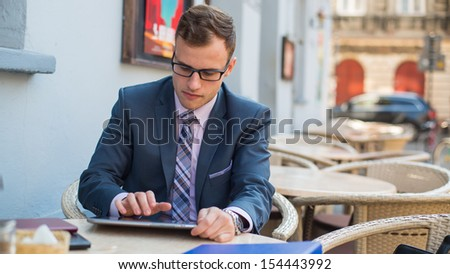 Young good-looking businessman sitting at coffee table, using tablet in cafe. - stock photo
