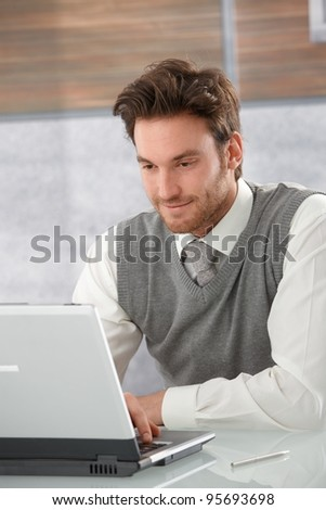 Young goodlooking casual office worker browsing internet on laptop, smiling.? - stock photo