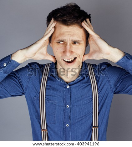 young goofy man with pimples pointing in studio - stock photo