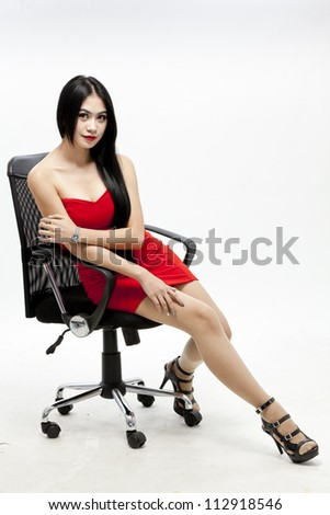 young gorgeous asian in red dress on the chair, isolated on white, studio shot - stock photo