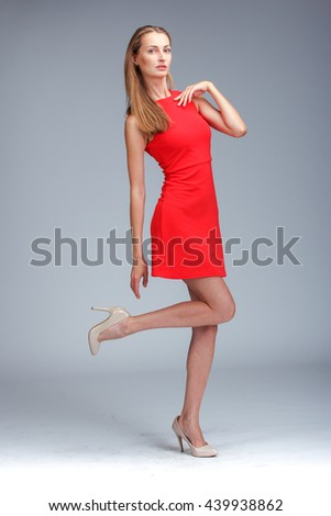 Young gorgeous caucasian blonde in red dress posing over grey background - stock photo