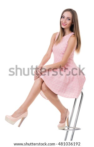 young gorgeous caucasian woman in pink dress on the chair