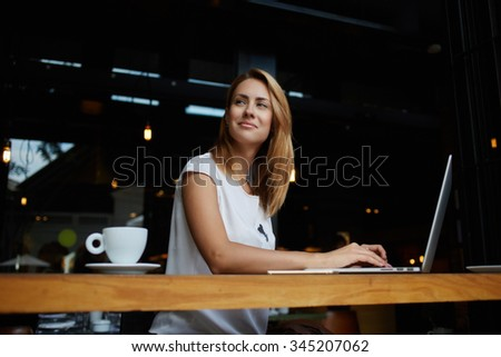Young gorgeous European woman with pretty face thinking about something while sitting with laptop computer in cafe bar, dreamy beautiful female using portable net-book during work break in coffee shop - stock photo